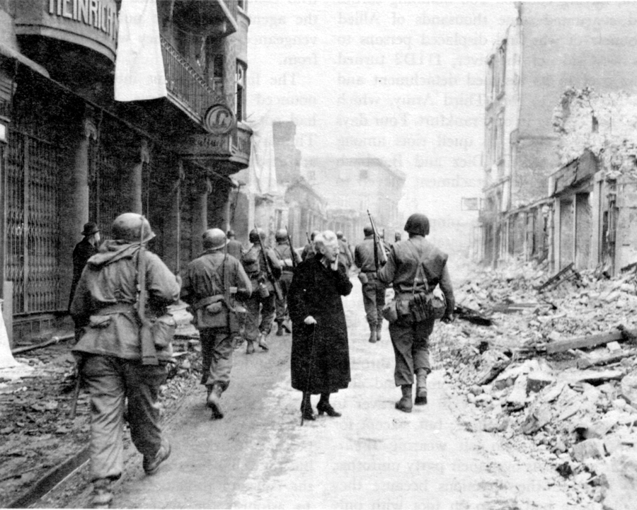 IN THE WAKE OF BATTLE a German woman surveys the wreckage of her property.
